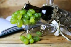 酒瓶书和玻璃葡萄 库存图片