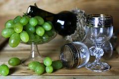 酒瓶书和玻璃葡萄 免版税库存照片