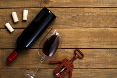酒瓶和玻璃拔塞螺旋和拔塞螺旋在木背景 与拷贝空间的顶视图 图库摄影