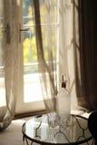 酒瓶和玻璃在表上在游廊附近 免版税图库摄影