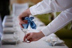 酒的侍者抹玻璃 免版税图库摄影