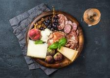 酒的意大利开胃小菜快餐在木盘子,黑暗的背景 库存图片