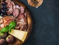 酒的意大利开胃小菜快餐在木盘子,黑暗的背景 免版税库存图片