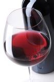 酒的瓶接近的玻璃 免版税库存图片