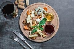 酒的-乳酪,蜂蜜,坚果,果酱乳酪盘子可口开胃菜,在一个轻的木板和一块玻璃服务用红葡萄酒  免版税库存图片