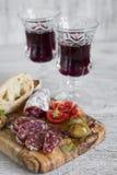 酒的-意大利香肠、橄榄、蕃茄和ciabatta可口开胃菜在橄榄色的委员会 库存图片