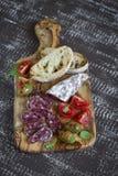 酒的-意大利香肠、橄榄、蕃茄和ciabatta可口开胃菜在橄榄色的委员会 免版税库存照片