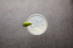 酒精与石灰片断和冰的玛格丽塔酒鸡尾酒顶视图灰色表面上 库存图片
