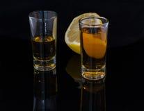 酒精两一个柠檬的射击和一半在黑暗的背景的 免版税库存图片