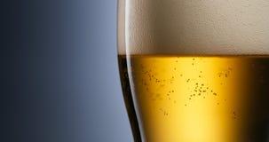 酒精中毒和瘾问题涌入玻璃的储藏啤酒 免版税图库摄影