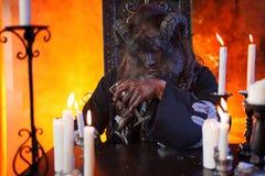 酒精中毒概念 妖怪的图象的人有坐在与手中的玻璃的桌上的垫铁的 图库摄影