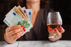 酒精中毒问题 在黑暗的被定调子的桌上的女性作为酒杯 库存照片