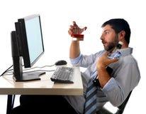酒精商人饮用的威士忌酒坐被喝在有计算机的办公室 免版税库存照片