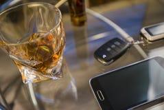 酒精饮料和汽车钥匙玻璃,在桌上,轻的背景 免版税库存照片