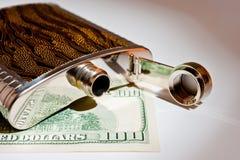 酒精饮料和美元的金属烧瓶特写镜头射击 免版税库存图片