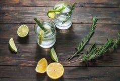 酒精饮料杜松子酒补剂鸡尾酒用柠檬、迷迭香和冰在土气木桌上 库存图片