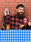 酒精饮料概念 方格的衬衣的人在砖墙背景准备饮料 有长的胡子的男服务员和 图库摄影