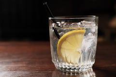 酒精饮料用柠檬和冰在一张老木桌上 免版税图库摄影