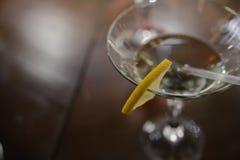 酒精饮料用柠檬在桌上站立 免版税库存照片