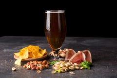 酒精饮料的特写镜头与快餐的 啤酒和咸开胃菜在饱和的黑背景 复制空间 免版税库存图片