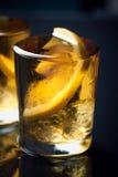 酒精鸡尾酒用白兰地酒、威士忌酒、柠檬和冰在小玻璃 图库摄影