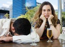酒醉人在酒吧睡觉,并且妻子是哀伤的 免版税图库摄影