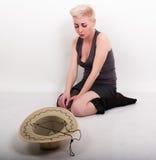 酒醉白肤金发的妇女坐地板,在她前面被拉扯的下来袜子是帽子 免版税库存照片