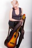 酒醉白肤金发的妇女坐椅子,拥抱吉他的被降下的长袜腿 免版税库存照片