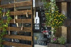 酒铺大厦的门面用木头、花和停止者装饰从酒在瓶 免版税库存照片