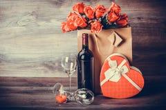 酒,玫瑰色和心脏作为在桌上的一件礼物 免版税库存照片