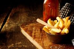 酥脆土豆片或楔子用番茄酱 库存照片