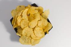 酥脆土豆片,在一块板材,在白色背景 特写镜头 顶视图 免版税库存照片