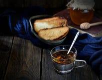 酥脆多士和茶在葡萄酒抢劫,蜂蜜和书在木背景 库存照片