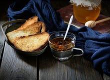 酥脆多士和茶在葡萄酒抢劫,蜂蜜和书在木背景 免版税图库摄影