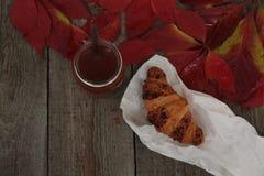 酥脆新月形面包用在木背景的热的可可粉 免版税图库摄影