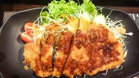酥脆油煎的猪肉和菜用调味汁在黑色的盘子, t 图库摄影