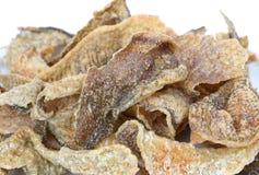 酥脆油煎的鱼皮肤用在白色背景的香料 图库摄影