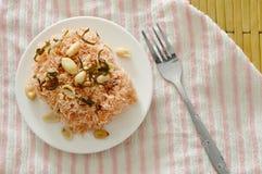 酥脆油煎的细面条用椰子提取乳脂顶部在板材的花生和切片柠檬叶子 免版税库存照片
