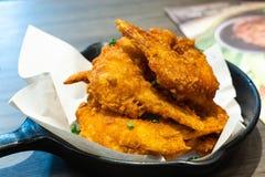 酥脆炸鸡在煎锅的纸飞过 免版税图库摄影