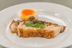 酥脆猪肉用在白色板材的煮沸的鸡蛋 免版税库存照片