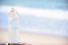 酥脆瓶在海滩的水 库存图片