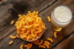 酥脆花生吹或轻碰快餐和杯子啤酒 库存图片