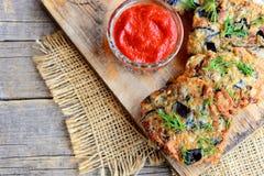 酥脆茄子汉堡用大蒜和莳萝在一个木板 在一个玻璃碗的西红柿酱 素食主义者茄子汉堡食谱 免版税库存照片