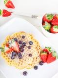 酥脆金黄新鲜的被烘烤的奶蛋烘饼冠上了用在丝毫的草莓 免版税库存照片