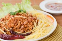 酥脆鲶鱼用绿色芒果沙拉,普遍的食物在泰国。 免版税库存图片
