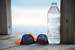 酥脆水瓶和对在木板走道的太阳镜 免版税库存照片