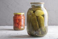 酱瓜和蕃茄在瓶子在白垩背景 免版税图库摄影
