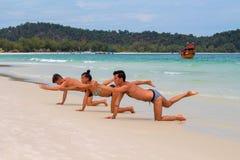 酸值荣海岛,柬埔寨- 2018年4月08日:做瑜伽的人们在白色沙子海滩由海 库存照片