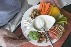 以酸奶、苹果切片、核桃和菜为特色的食物健康板材举行供以人员手 免版税库存图片