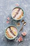 酸奶健康早餐用香蕉、chia种子、椰子剥落和杏仁在灰色背景,装饰用桃红色 库存照片